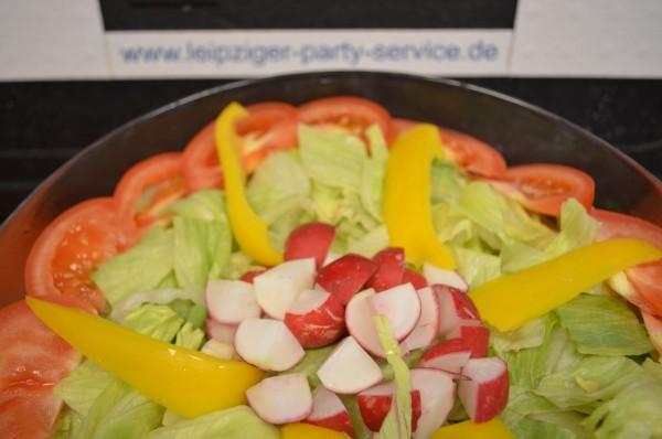verschiedene Blattsalate mit Tomaten, Gurken und zwei verschiedenen Dressings